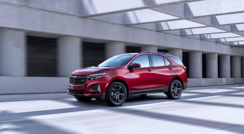 A red 2022 Chevy Equinox RS is driving past a grey building after leaving a Chevy dealer.