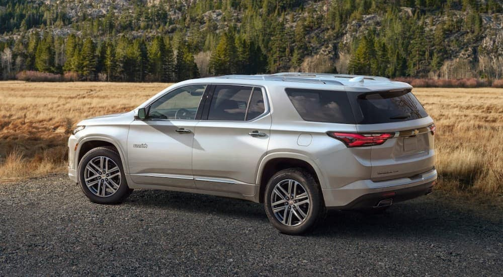 A silver 2022 Chevy Traverse is parked in front of a field and pine trees.