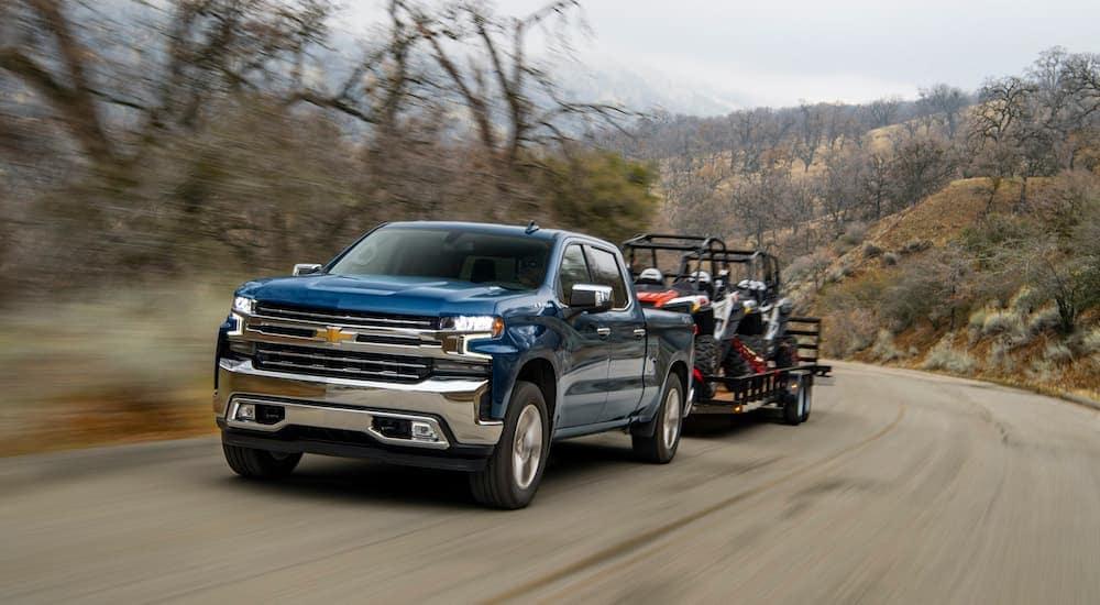 A dark blue 2020 Chevy Silverado Duramax Diesel is towing a trailer with two UTVs down a dirt road.