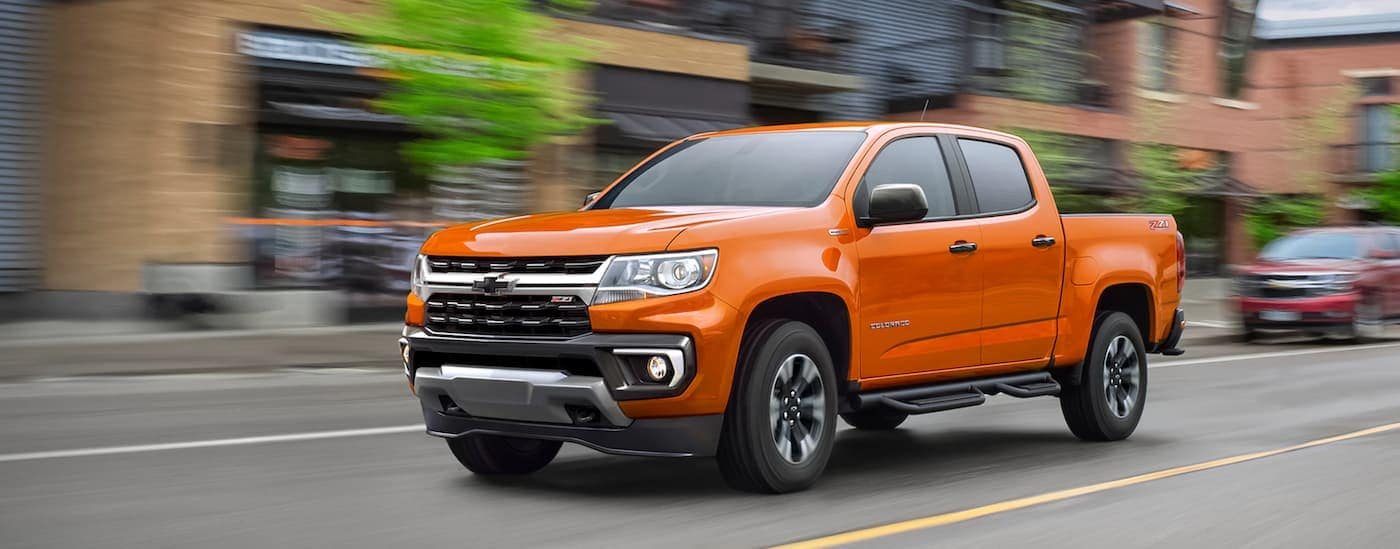 An orange 2021 Chevy Colorado is driving on a city street.