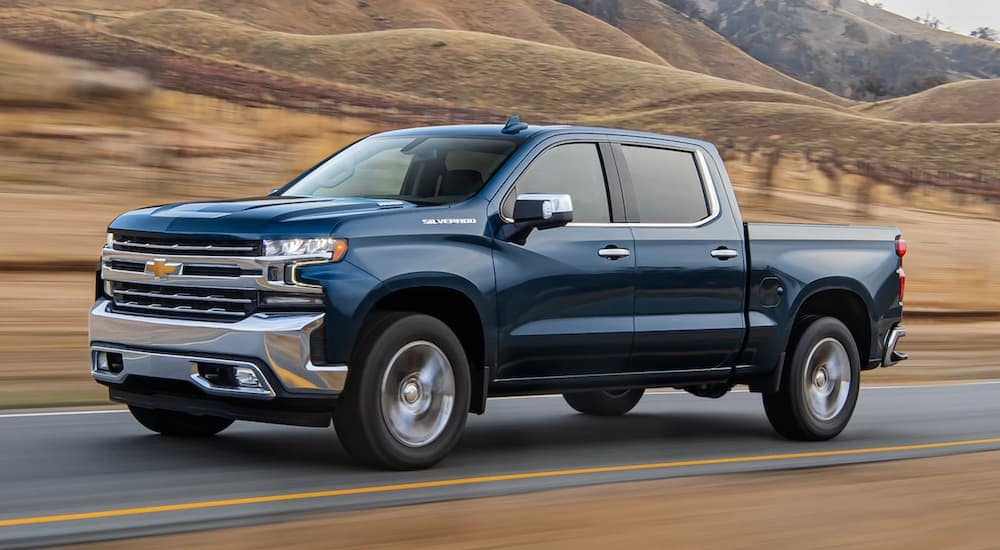 A blue 2021 Chevy Silverado 1500 is driving past brown grass after leaving a Chevy diesel truck dealer.
