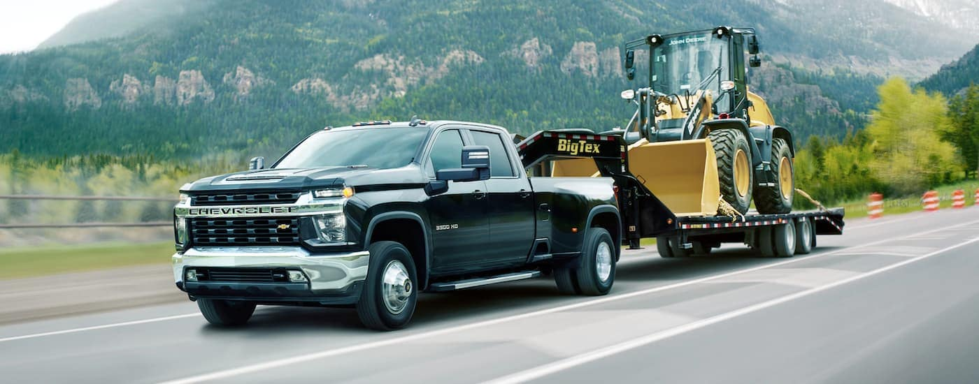 A black 2021 Chevy Silverado 3500 is towing heavy machinery past a mountain and orange cones.