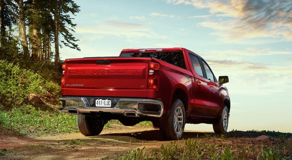 A red 2021 Chevy Silverado LT Z71 is shown from the rear angled right, parked in the woods.