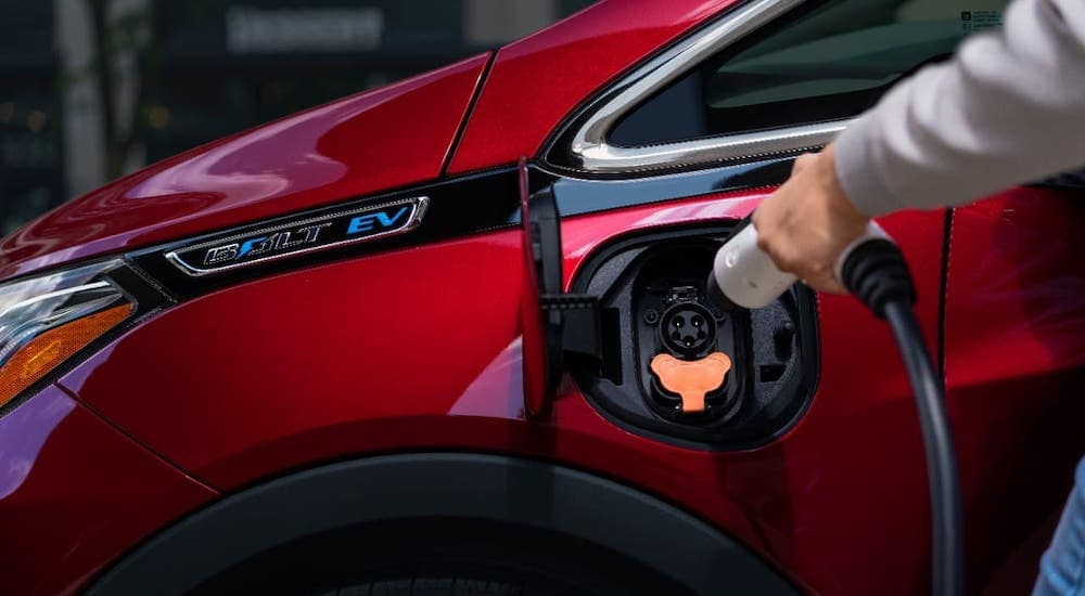 A common sight for Chevy EVs, a hand is shown plugging in a red 2020 Chevy Bolt EV.