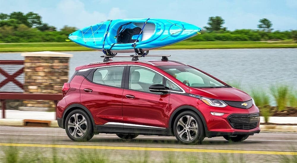 A red 2020 Chevy Bolt EV is driving past a lake with a kayak on the roof.