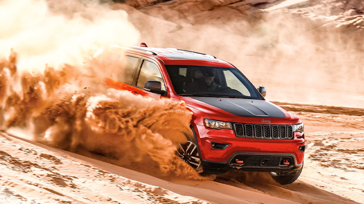 2021 Jeep Grand Cherokee Trailhawk surrounded by dust clouds as it drives on sandy terrain