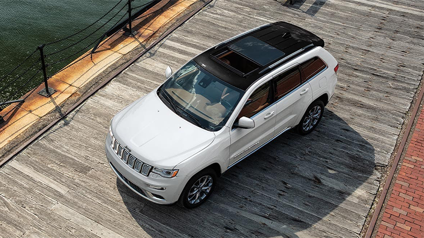 2021 Jeep Grand Cherokee Summit in the color Ivory 3 Coat parked on a boardwalk