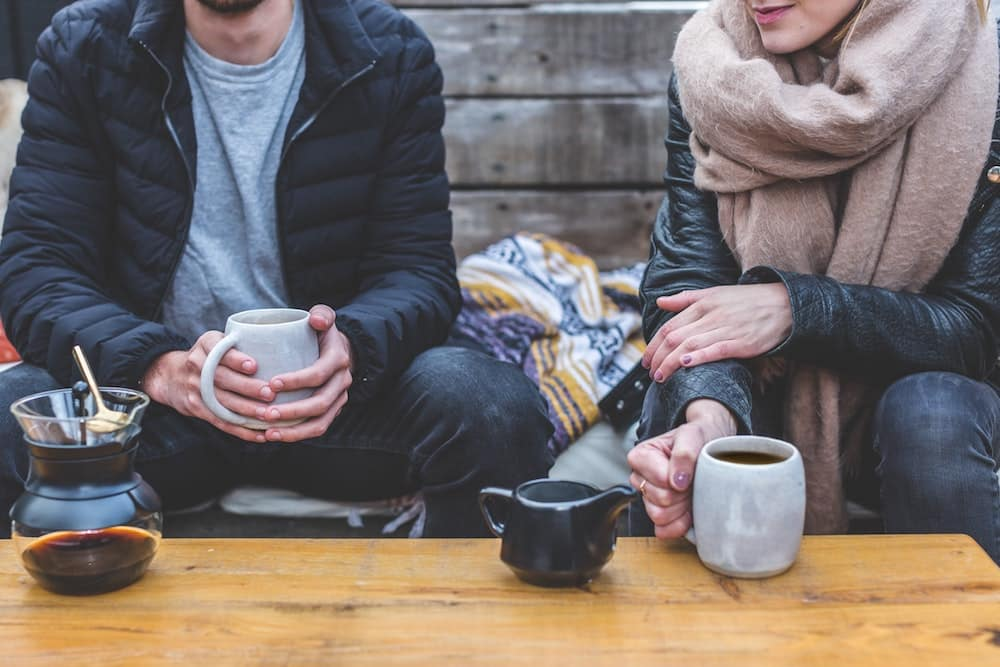 Couple Drinking Coffee and Tea on a Bench