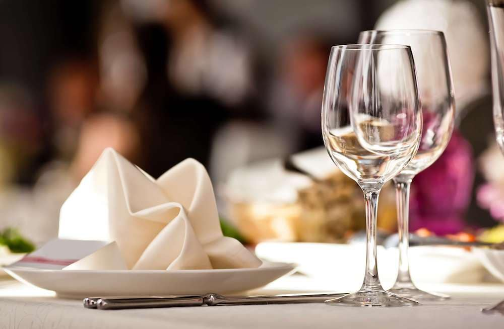 Two empty wine glasses next to napkin on empty white plate in restaurant