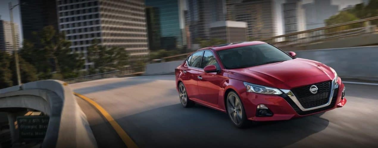 A red 2021 Nissan Altima is driving on a city street.