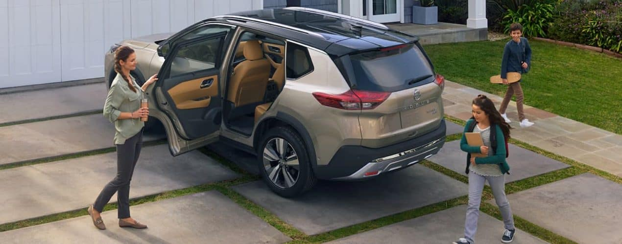 A mom is holding the door of a tan 2021 Nissan Rogue open for her kids in the driveway.