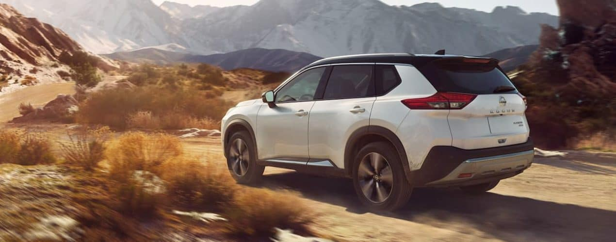 A white 2021 Nissan Rogue is on a dirt path in front of mountains.