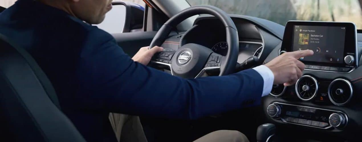 A man is using the touchscreen in a 2021 Nissan Sentra.