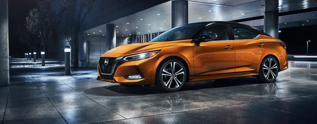 An orange 2021 Nissan Sentra is parked in parking garage at night.