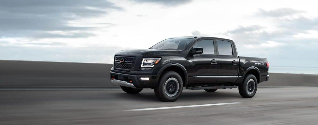 A black 2021 Nissan Titan is driving on a highway.
