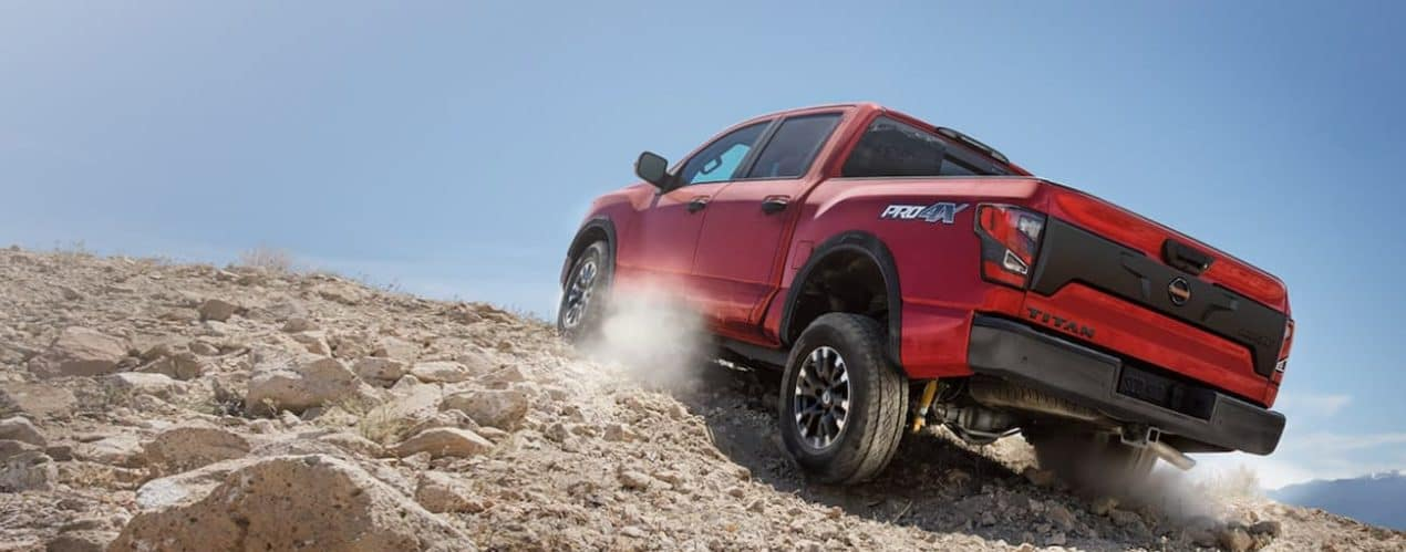 A red 2021 Nissan Titan Pro-4X is off-roading up a dirt hill.