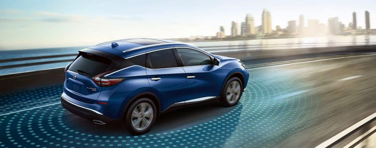 A blue 2021 Nissan Murano Platinum is shown driving down a highway with simulated sensor lines.