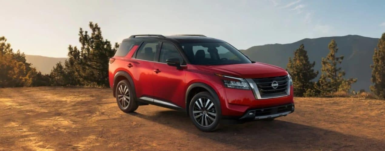 A red 2022 Nissan Pathfinder is parked on dirt overlooking mountains.
