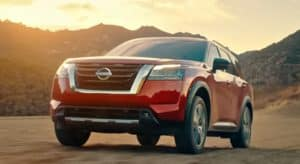 A red 2022 Nissan Pathfinder is driving past mountains at sunset.