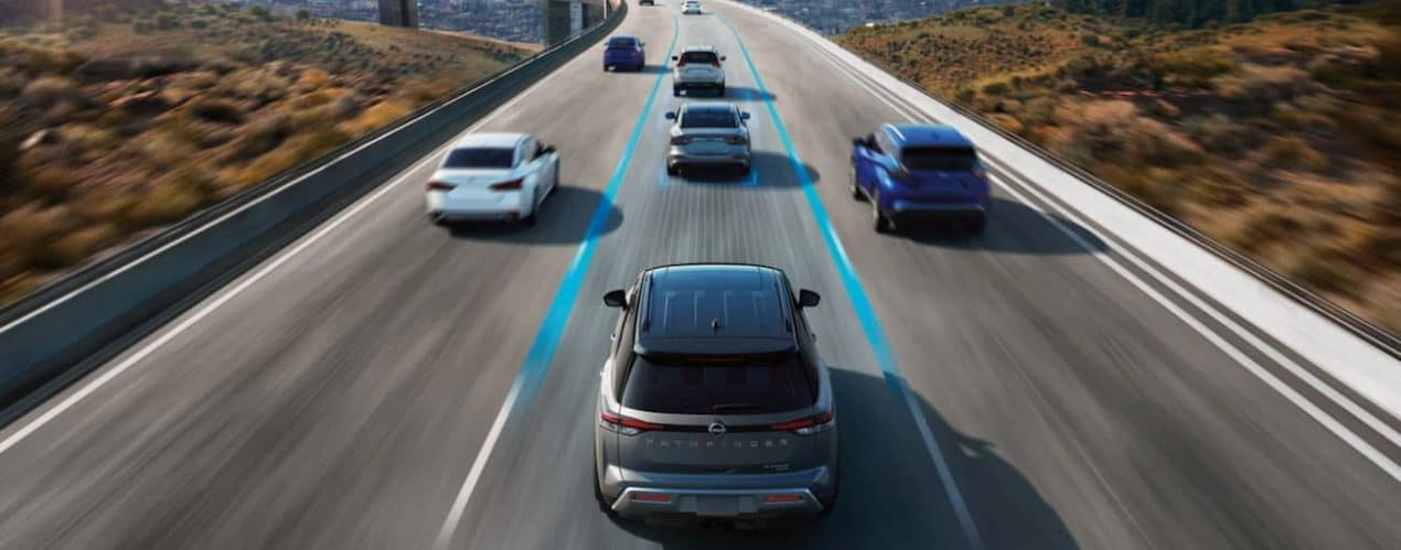 A grey 2022 Nissan Pathfinder is driving on a multi-lane highway with simulated blue lines for lane safety features.