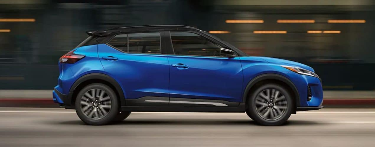 A blue 2021 Nissan Kicks is shown from the side driving through a city.
