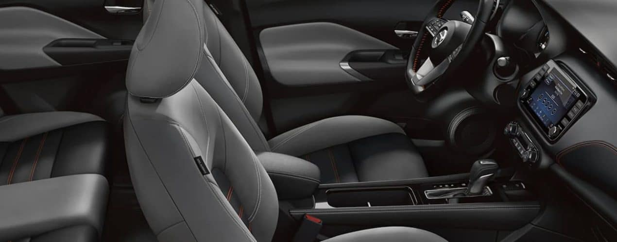 The black interior of a 2021 Nissan Kicks shows the front seats and steering wheel.