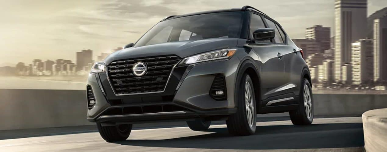 A silver 2021 Nissan Kicks is driving through a city.