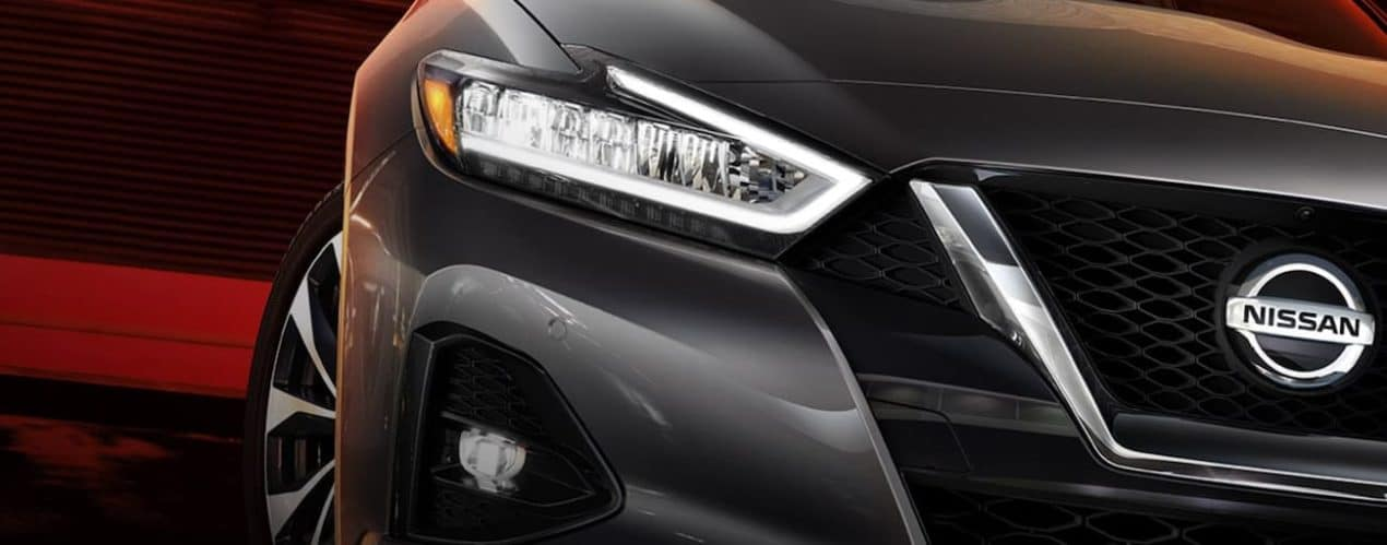 A close up shows the passenger headlight of a grey 2021 Nissan Maxima.