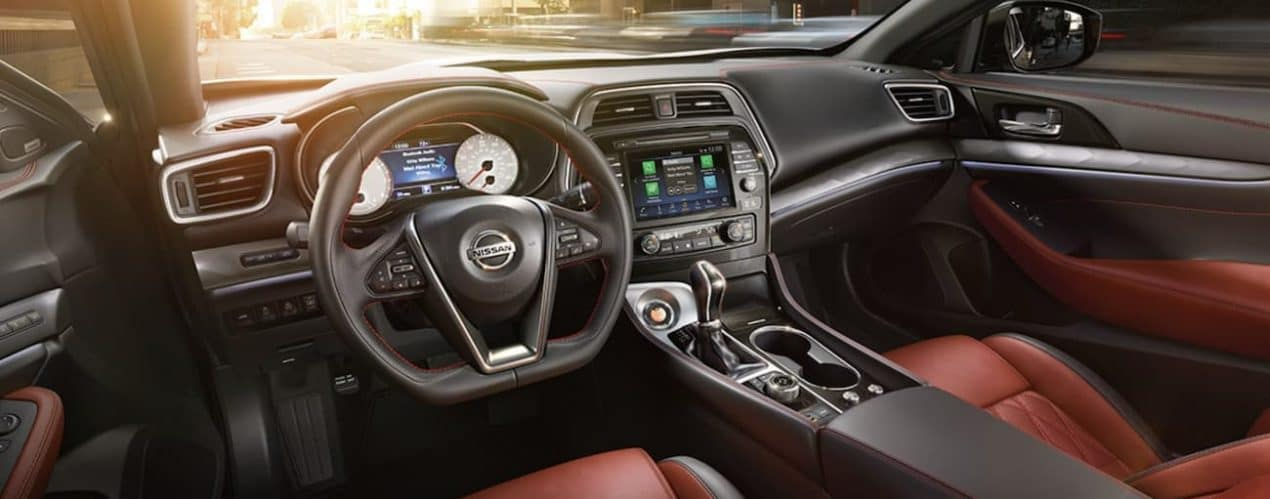 The interior of a 2021 Nissan Maxima shows the steering wheel and infotainment screen.
