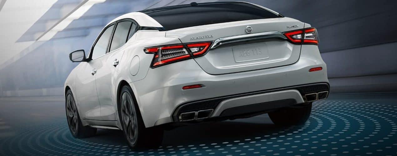 A white 2021 Nissan Maxima is driving through a city.