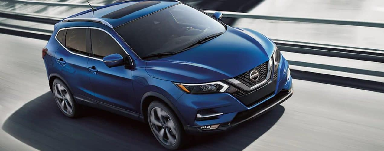 A blue 2021 Nissan Rogue Sport is shown driving on a highway.