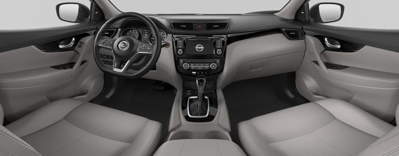 The interior of a 2021 Nissan Rogue Sport shows the steering wheel and infotainment screen.