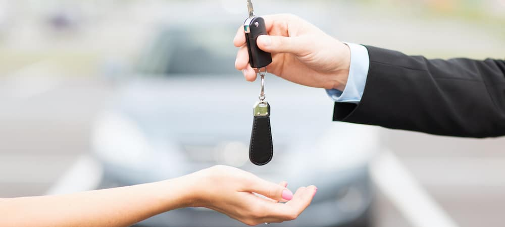 Car salesperson handing over car keys to buyer
