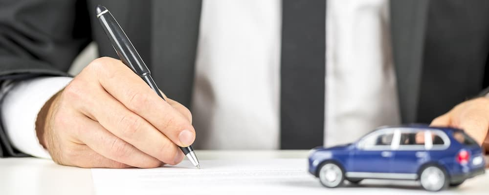 Man in suit signing papers with blue toy SUV on table; car financing concept