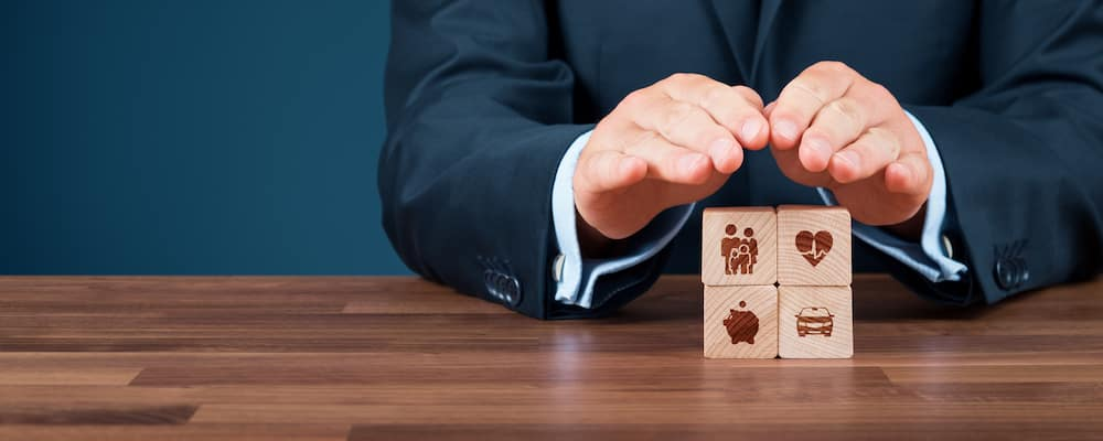 Hands of businessman covering four wooden blocks to convey GAP insurance concept
