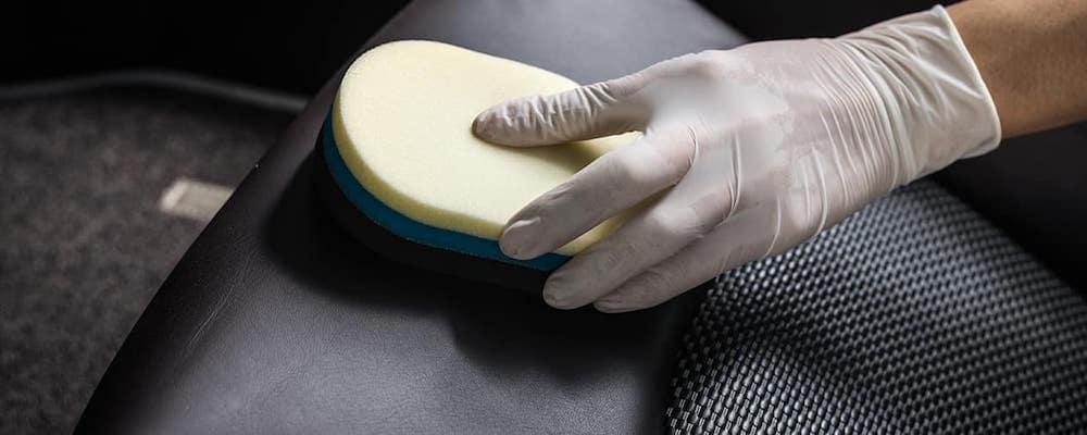 Close on gloved hand cleaning leather car seat