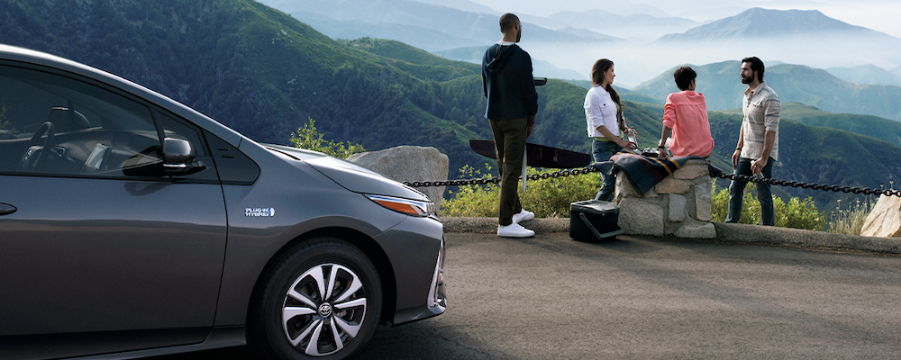 Four friends looking at mountains with silver Toyota Prius Prime in foreground