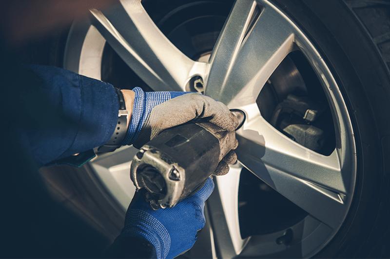 technician installs new car tire