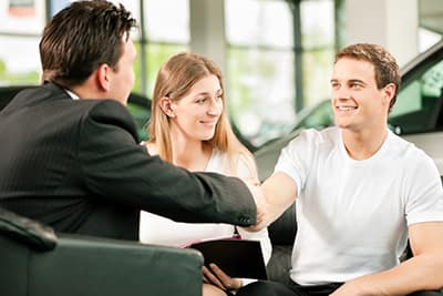 Dealership, the dealer is handing auto keys to a young couple, they are excited, cars standing in the background