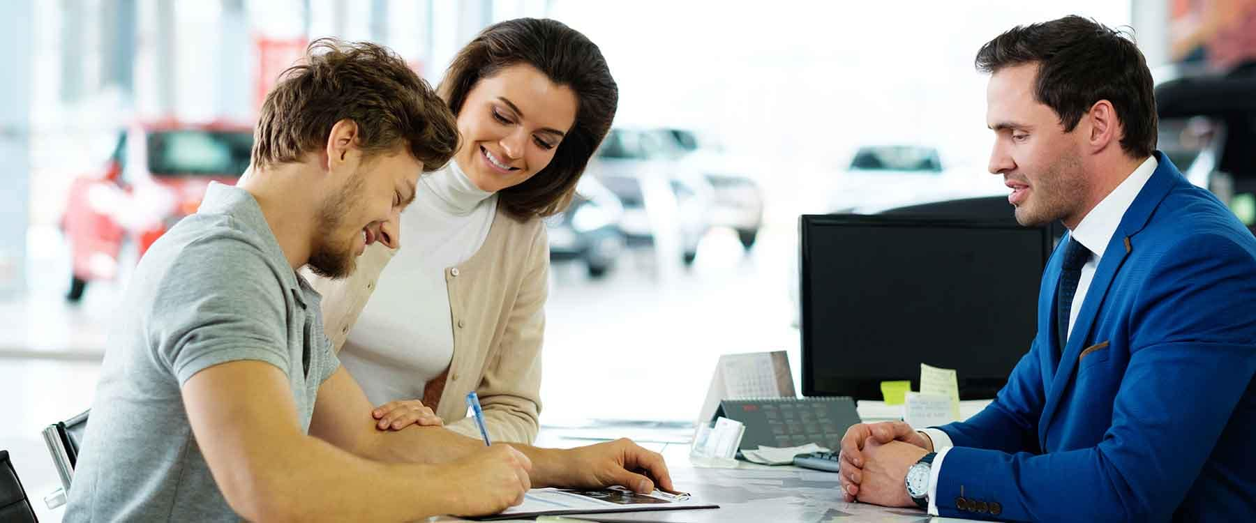 Beautiful young couple signs documents at dealership showroom