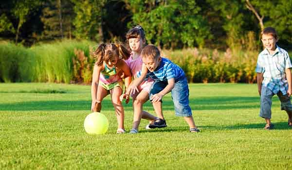 Kids playing with a ball in a sports field