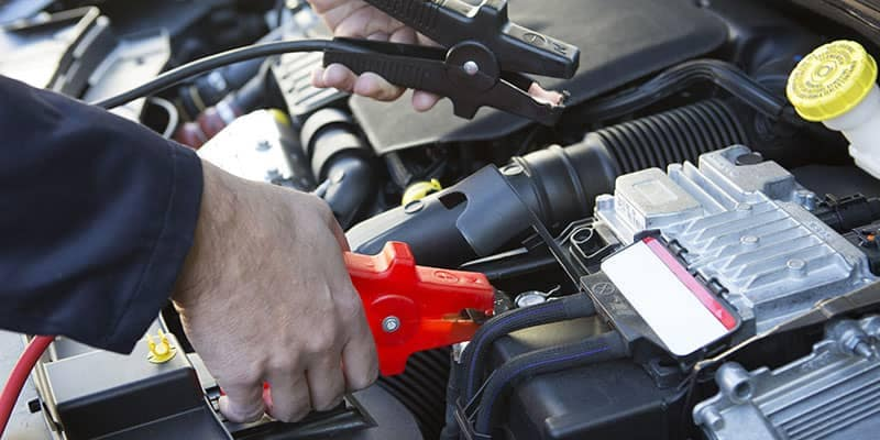 Close-Up Of Mechanic Attaching Jumper Cables To Car Battery