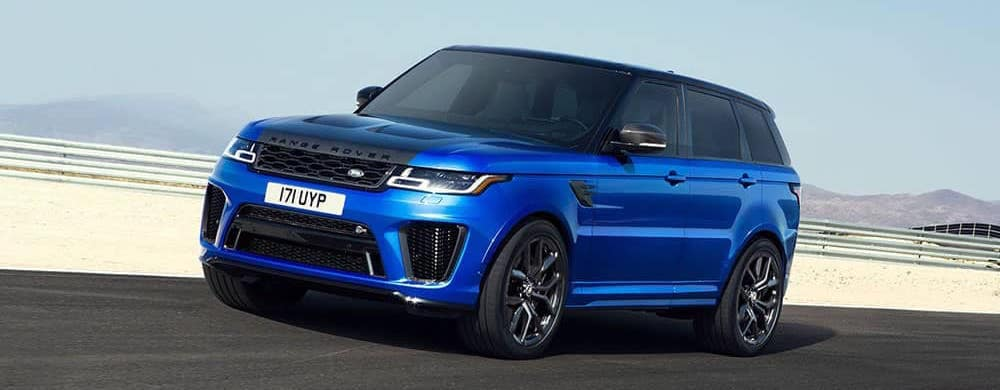 blue Range Rover driving down the highway