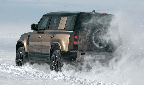 Land Rover defender driving in snow rearview