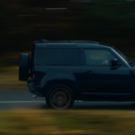 The new Land Rover Defender V8 driving on a highway.