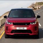 A red Land Rover Discovery Sport driving on a highway.