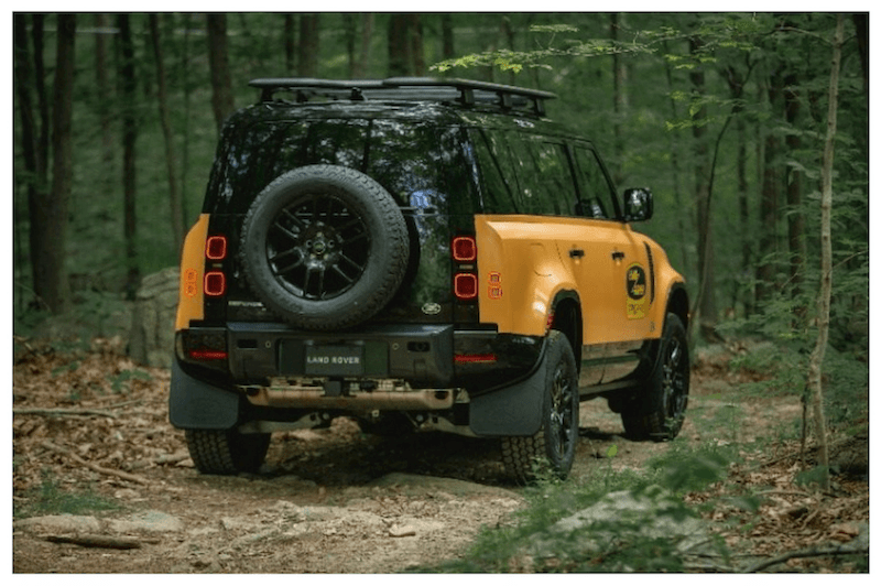 Rear of 2022 Land Rover Defender Trophy parked in wooded area