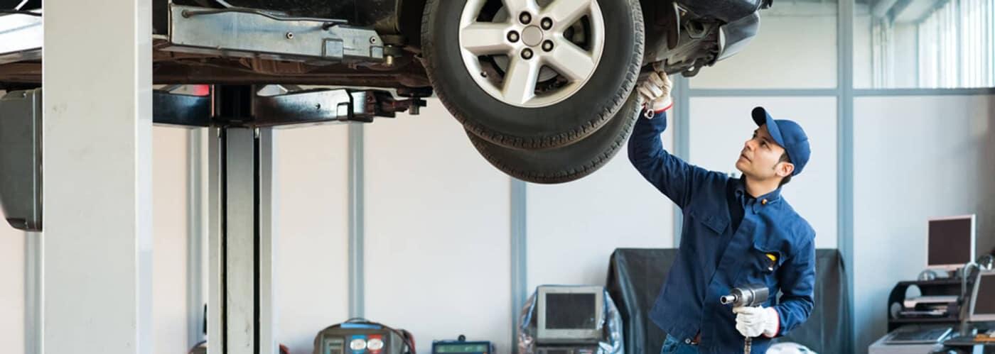 A car service tech working under a vehicle