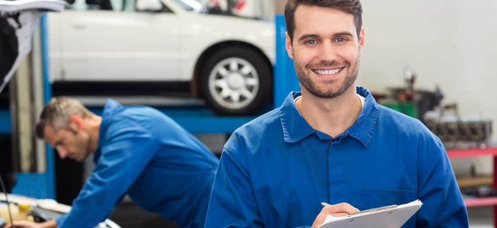 Mechanic in blue shirt holding clipboard