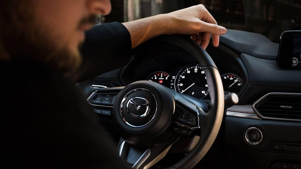 Man with his hand on the steering wheel of a 2019 Mazda CX-5